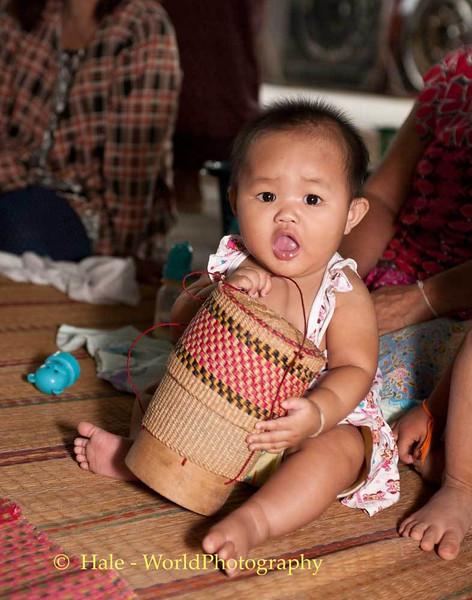 Lao Loum Baby Plays During Buddhist Merit Making Ritual