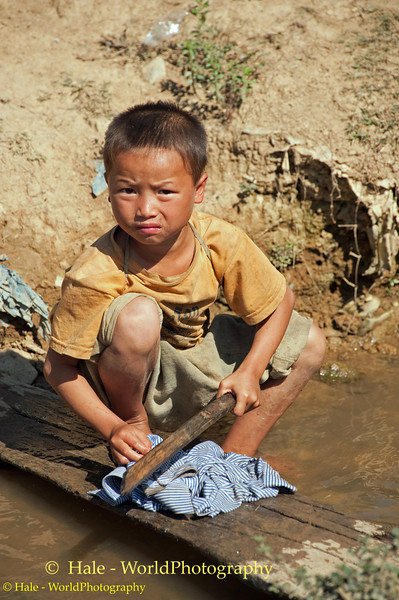Lanten Boy Washing Clothes Outside His Home in Ban Pakha, Laos