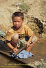 Lanten Boy Washing Clothes Outside His Home in Ban Pakha, Laos