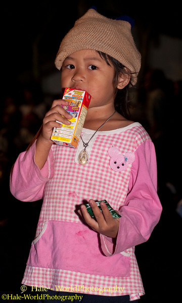 A Young Lao Loum Villager Enjoys a Snack At A Mahlam Lao Show