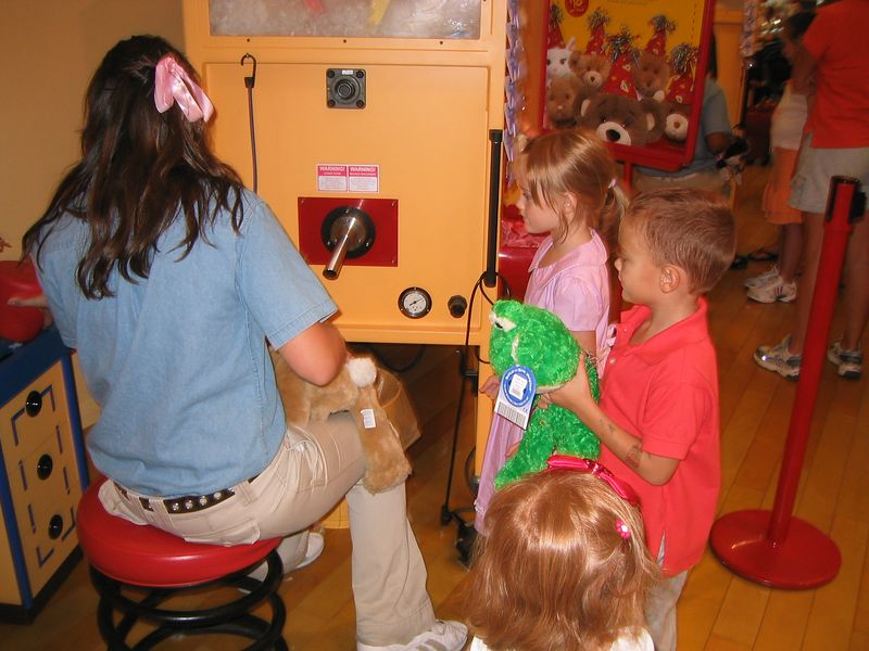 This was our first time at the Build A Bear Workshop.  Caroline is waiting to have her bunny stuffed.  August 3, 2005