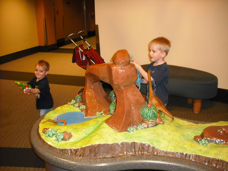 "Zach being mischievous - he had just growled and had the dinosaur ""eat"" Alex.  Alex unphased."
