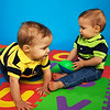 Two adorable toddlers crawling on a colorful letter mat.
