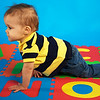 An adorable toddler crawling on a colorful letter mat.