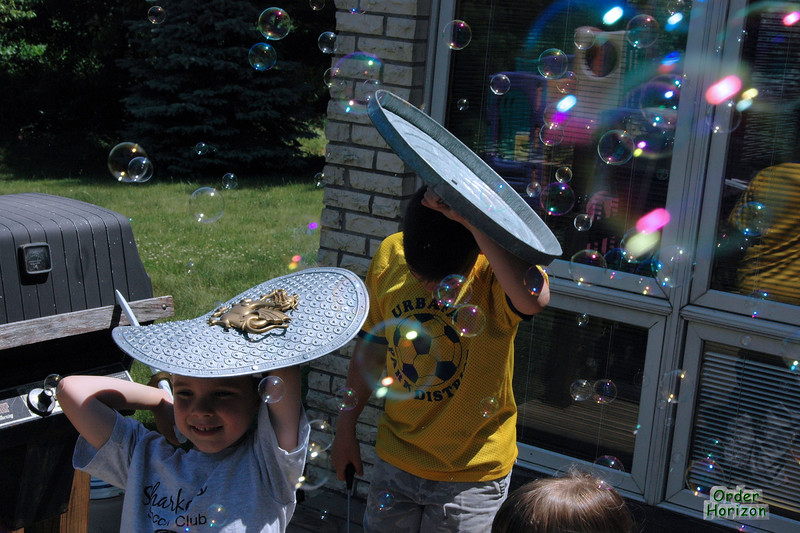 The boys cower under their shields from the rain of bubbles