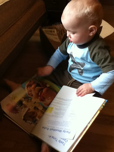 Reading a cookbook at home. Theo thought it was a great book because it had photos of food on every page.