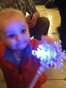 """Theo at the mall downtown waiting for the """"snow"""" to fall; we bought these light up snowflakes on a stick for a dollar each."""