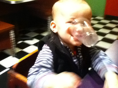 Theo playing with the plastic cups by holding them in his mouth