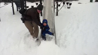 Sliding at the park playground in the snow