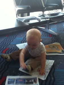 Reading the newspaper at the airport before our flight to Atlanta