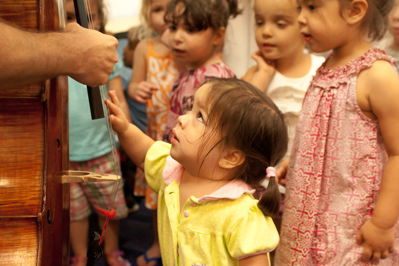 Audriana strums the strings of a cello when Kurt Baldwin of Arianna String Quartet teaches children at University City Children's Center how music can tell a story.