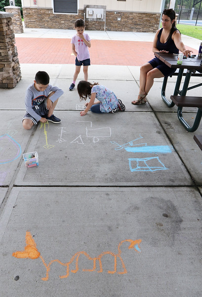 July 21, 2021 -- Tyler Lefebvre, 7, and his twin sisters Sara, rear, and Kate Lefebvre, 5, of Wilmington, do chalk drawings with their nanny Hannah Paoletti, in the pavilion at Yentile Farm Recreational Facility in Wilmington. They did the centipede in the foreground after seeing a real one.  SUN/Julia Malakie