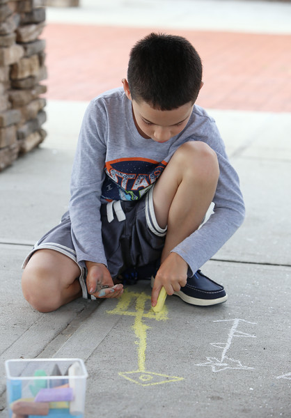 July 21, 2021 -- Tyler Lefebvre, 7, of Wilmington, does chalk drawings in the pavilion at Yentile Farm Recreational Facility in Wilmington.  SUN/Julia Malakie