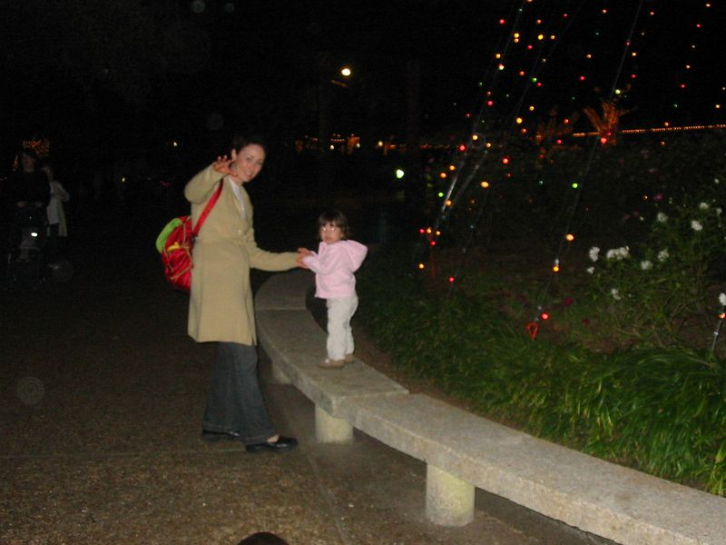 Kelly and Olivia playing on the benches around the large, light Christmas tree.