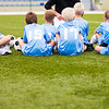Football soccer match for children. Boys and coach sitting on green grass.