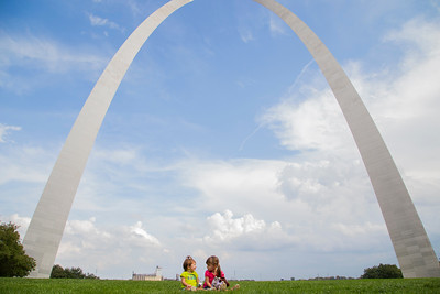 the girls sitting in front of the Arch