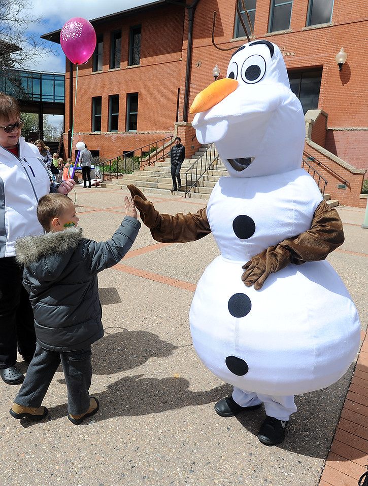 Caden Guthrie, 5, high-fives a snowman mascot Monday, April 18, 2016, during Children's Day activities at the Civic Center in Loveland. (Photo by Jenny Sparks/Loveland Reporter-Herald)