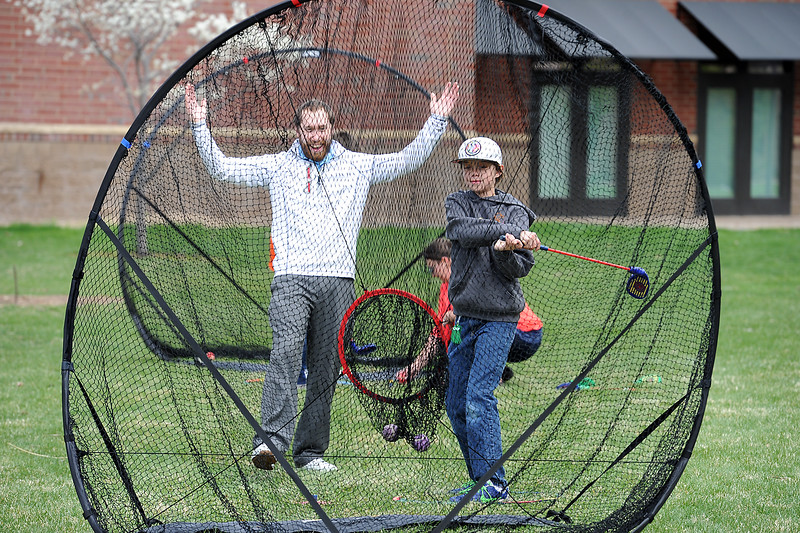 Lanny Cameron, left, a golf instructor with the city of Loveland, reacts as Tavin Adamson, 11, hit his second ball into the center hole Monday, April 18, 2016, during Children's Day activities at the Civic Center in Loveland. (Photo by Jenny Sparks/Loveland Reporter-Herald)