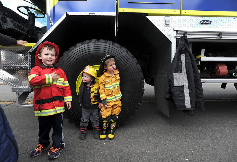 All dressed in their firefighter gear, Joseph McDevitt, 5, left, makes sure his new firefighter sticker badge is secured to his coat as his little brothers Patrick McDevitt, 2, center, and Michael McDevitt, 4, right, size themselves up to the tire of an airport firetruck Monday, April 18, 2016, during Children's Day activities at the Civic Center in Loveland. (Photo by Jenny Sparks/Loveland Reporter-Herald)