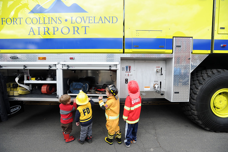 From left Peter Ross, 1, and his cousins Patrick McDevitt, 2, Michael McDevitt, 4, and Joseph McDevitt, 5, check out the tool compartments of an airport firetruck Monday, April 18, 2016, during Children's Day activities at the Civic Center in Loveland. (Photo by Jenny Sparks/Loveland Reporter-Herald)