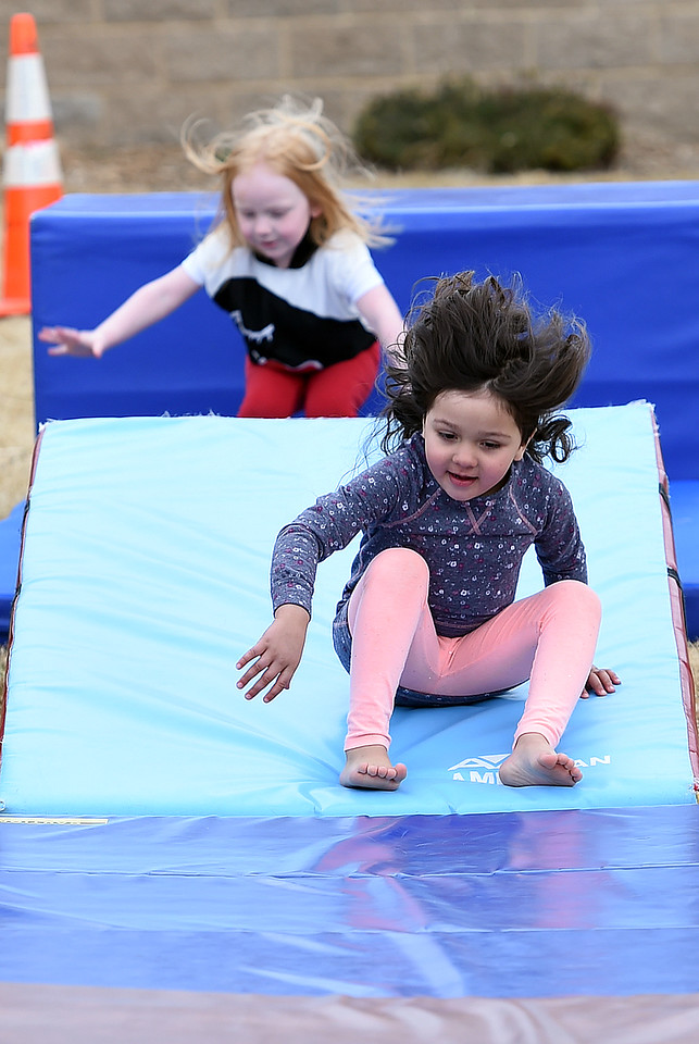 Julianna Ybarra, 4, front, and Josephine Short, 4, do somersaults at the gymnastics area Friday, March 9, 2018, during Children's Day outside the Chilson Recreation Center in dowtown Loveland.  (Photo by Jenny Sparks/Loveland Reporter-Herald)