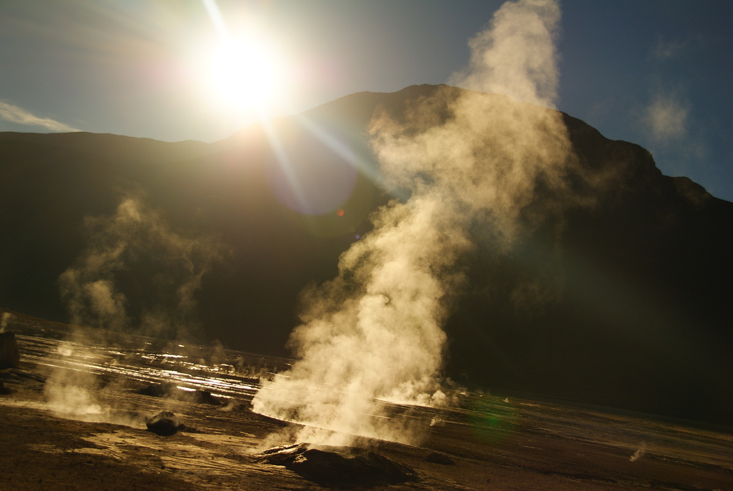 A photo of the El Tatio geysers in the Atacama desert with the sun rising - Chile.  Travel photo from the Atacama Desert, Chile.