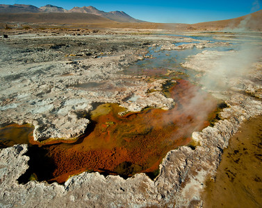 Tatio Geysers with steam rising in early morning hour, with crust surrounding scalding hot water colored from mineral deposits. Atacama, Chile