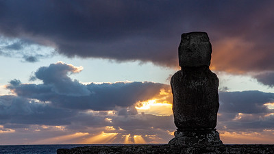 Standing alone, the solitary moai Ahu Tahai frames the sunset over the Pacific Ocean on Easter Island.