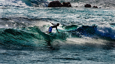 A surfer finds his ride just inside the reef at Hanga Roa, Easter Island.