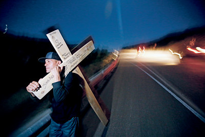 Joshua Sandoval of Santa Fe, carries his cross on his pilgrimage to the Santuario de Chimayo on Good Friday, April 19, 2019. Sandoval started walking at 6pm in La Ciénaga, almost 45 miles with his 30 lbs cross. This is his 21st year making the pilgrimage for his family. Luis Sánchez Saturno/The New Mexican