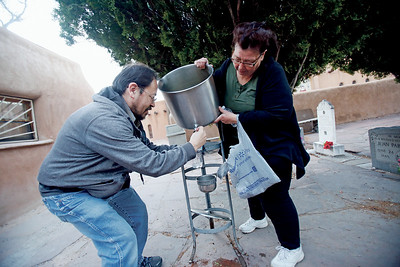"""Diane Cordova, right,of Albuquerque, helps Robert Martinez, of Albuquerque, get the last of the holy water before starting her pilgrimage on Good Friday, April 19, 2019. Cordova will drive to Pojoaque and come back to the Santuario de Chimayo. She has been walking since she was a kid and It's a family tradition for her. """"Rain or snow, there is nothing that is gonna stop us,"""" she said. Martinez is on his 5th or 6th years, he isn't sure. But he does it to honor of God. Luis Sánchez Saturno/The New Mexican"""