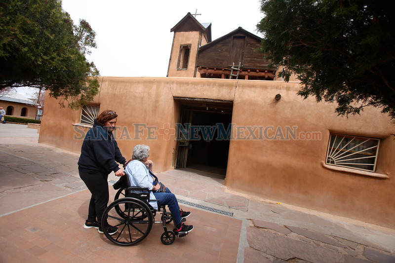 """Sandra Cisneros, pushes her mom Sofia Cisneros in front of the Santuario de Chimayo on Monday, March 26, 2018. Cisneros attributes her cancer survival to her faith. """"The lord is the one that healed me."""" She said. """"He has a plan for us all."""" Luis Sánchez Saturno/The New Mexican"""