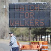 Mark Senteney, a teacher at Pojoaque Valley HighSchool, walks past a road sign warning motorists about pilgrims as he makes his pilgrimage to Chimayo from Española for the 5th time on Thursday, March 29, 2018. Luis Sanchez Saturno/The New Mexican