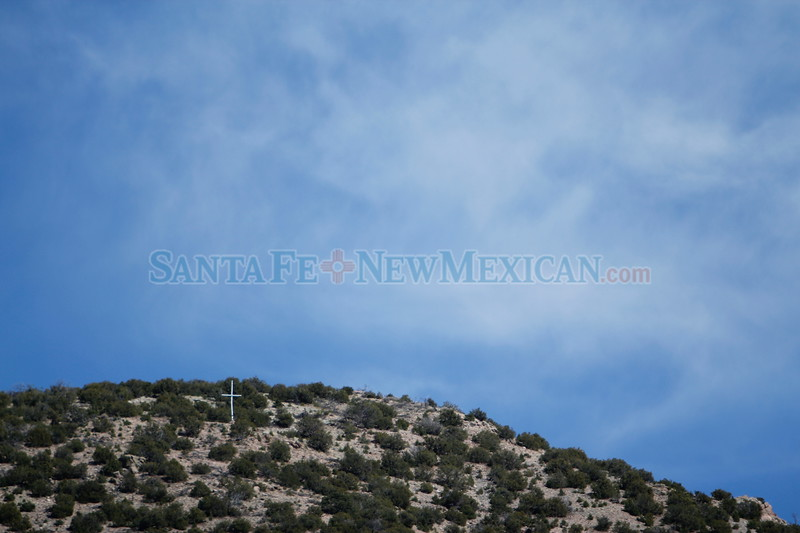 A cross at the top of the mountains overlooking the Santuario de Chimayo on Wednesday, March 28, 2018. Luis Sánchez Saturno/The New Mexican