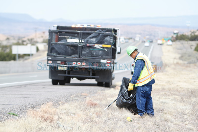 Miko Quintana, with Department of Transportation's Santa Fe Patrol, picks up trash on 285 North in preparation for the Chimayo pilgrimage on Monday, March 26, 2018. Luis Sánchez Saturno/The New Mexican