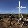 Nathan Leyba, left of Albuquerque Shantelle Quintana of Albuquerque and Linda Medina of Las Vegas, NM, paint one of the crosses on Cundiyo Rd on Thursday, March 29, 2018. Luis Sanchez Saturno/The New Mexican