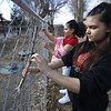 Lexus Thompson, 13, who did the pilgrimage for the first time, and Lisa Perez, 15, both of Albuquerque, put crosses on a fence behind the Santuario de Chimayo on Thursday, March 29, 2018. Luis Sanchez Saturno/The New Mexican