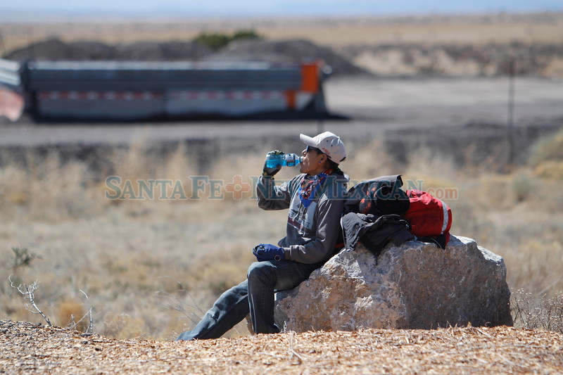 Joseph Benavidez of Santo Domingo Pueblo takes a break  while he hikes along I-25 at the top of La Bajada on his eight year going making his pilgrimage to the Santuario de Chimayo for holy week on Wednesday, March 28, 2018. Luis Sánchez Saturno/The New Mexican