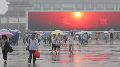 """Enormous video screens on Tienanmen Square. The colors and images were very vivid on such a rainy gray day. The screen says here """"Beijing"""""""