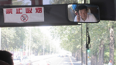 Bus driver making calls to find more passengers for the bus