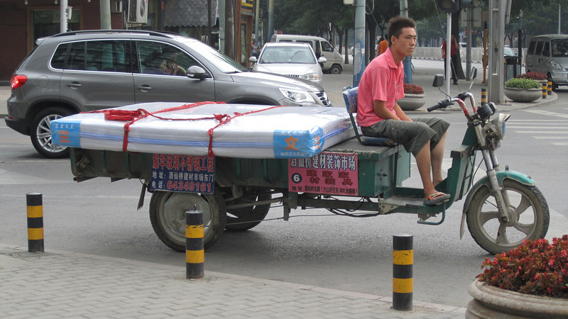 Yes, he's delivering a large mattress on the three-wheeler