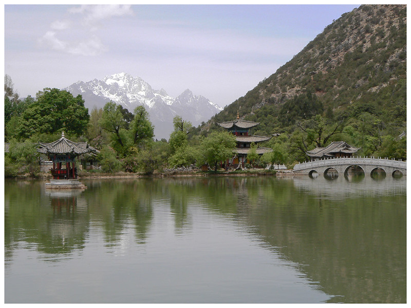 in the background 18,359 ft high Black Dragon Snow Mountain. The spring- fed pond is the water source for Lijiang