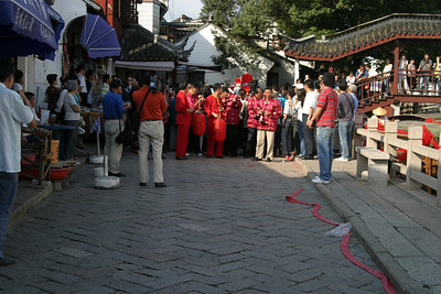 The procession preparing to set out.  In front are musicians with traditional Chinese instruments.  Further back, the top of the sedan chair with the bride can be seen.  Note the long string of firecrackers in the bottom right, waiting to be lit.