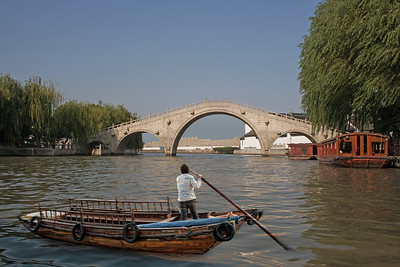 a riverboat in Suzhou, China with a three-arched bridge in the background