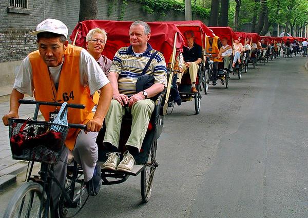 Bicycle rickshaws carrying tour busload through hutongs