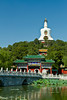 An arched bridge over the lake and The Bai Ta (White Pagoda), a 40 m high stupa in Beihai Park in Beijing, China.