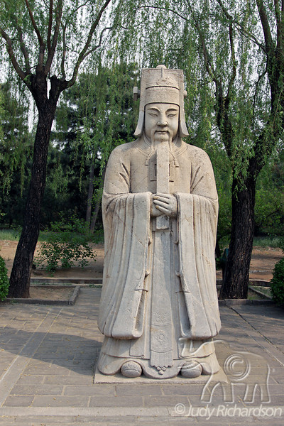 Human statue is dressed in ceremonial garment, appropriate for the presence of the emperor. on the Ming Tombs grounds