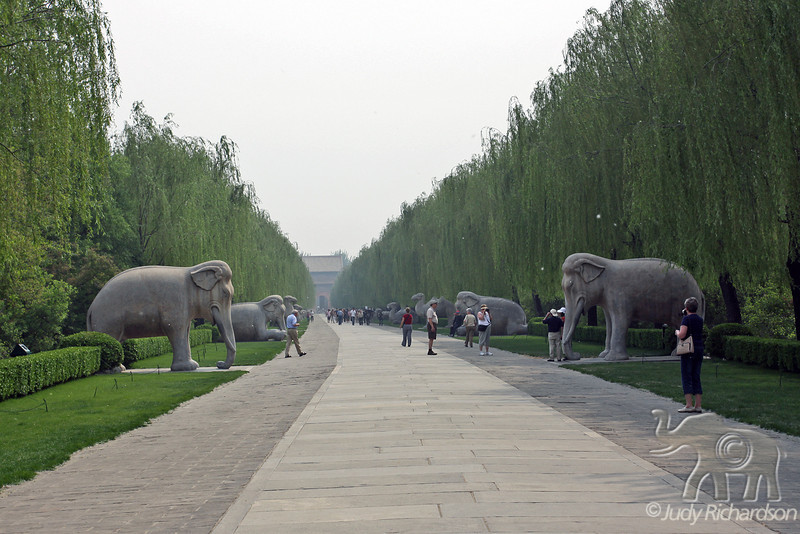 The entrance to the Ming Tombs, a long and celebrated shen dao (spirit way) is lined with statues of guardian animals and officials. The Sacred Way path is slightly curved to fool malevolent spirits.