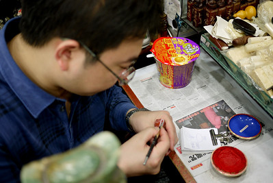 An artisan hand-crafting a marble stamp, the Pearl Market in Beijing, China.