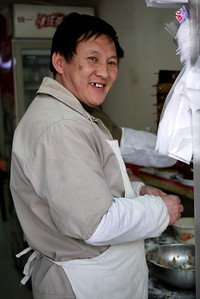 Smiling dumpling vendor at a tiny shop in Beijing, China.